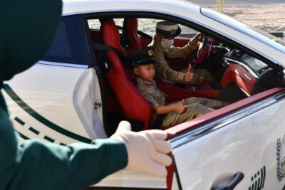 """بالصور.. """"شرطة دبي"""" تحقق أمنية طفل وتصطحبه في جولة بإحدى دورياتها الفارهة"""
